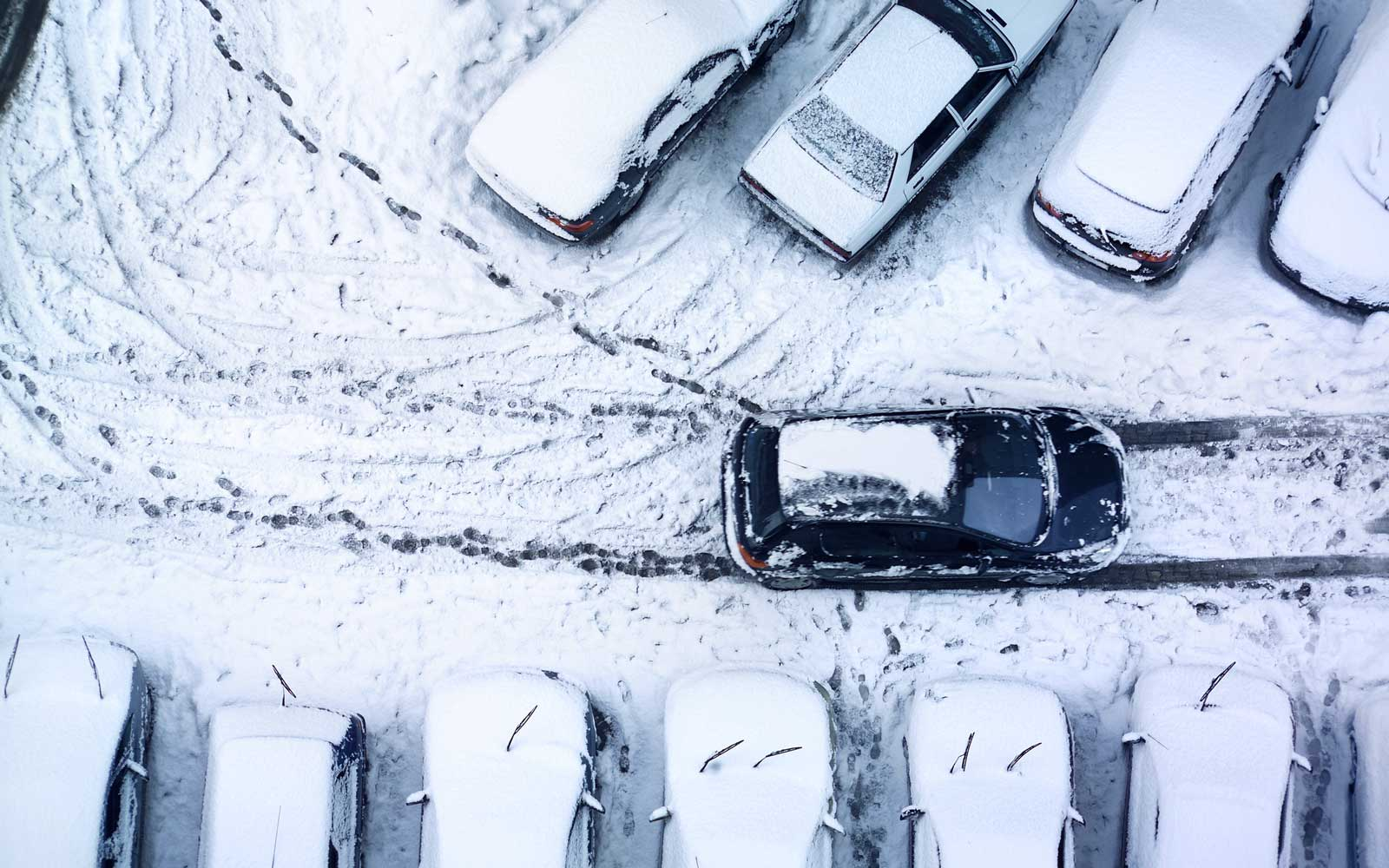 Snowy cars in a parking lot
