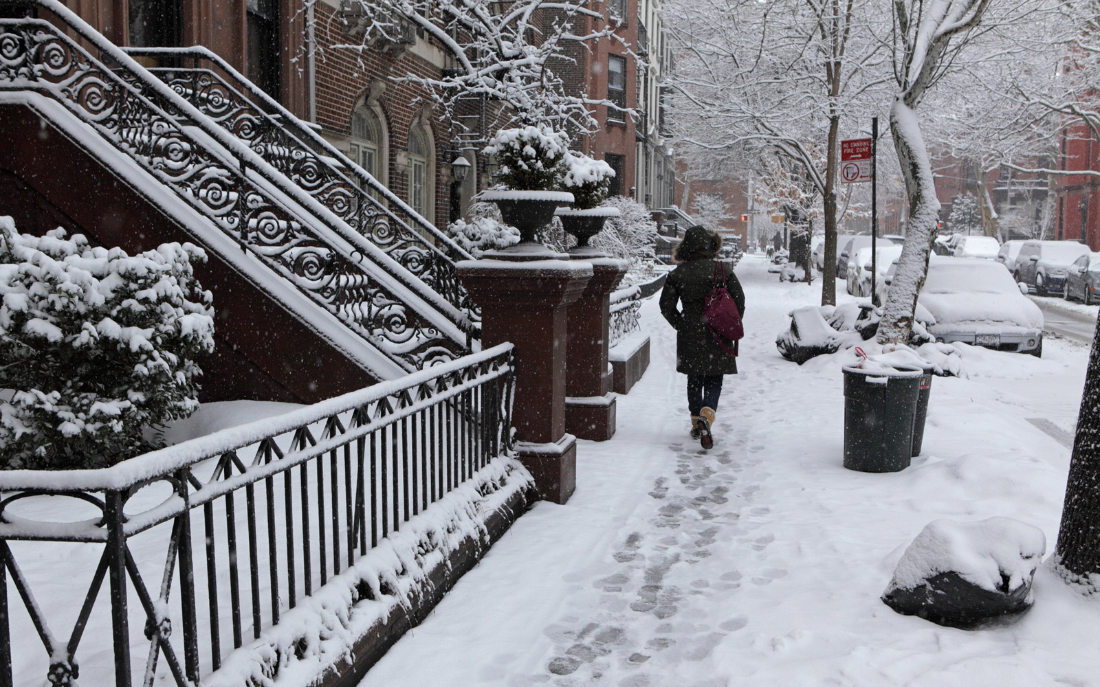 Woman walks along Brooklyn Heights street in winter snow storm