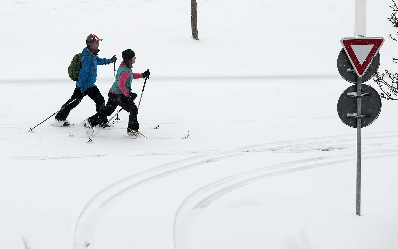 A couple ski on a snow covered street of Biarritz, southwestern France, on February 28, 2018, after heavy snow fall.