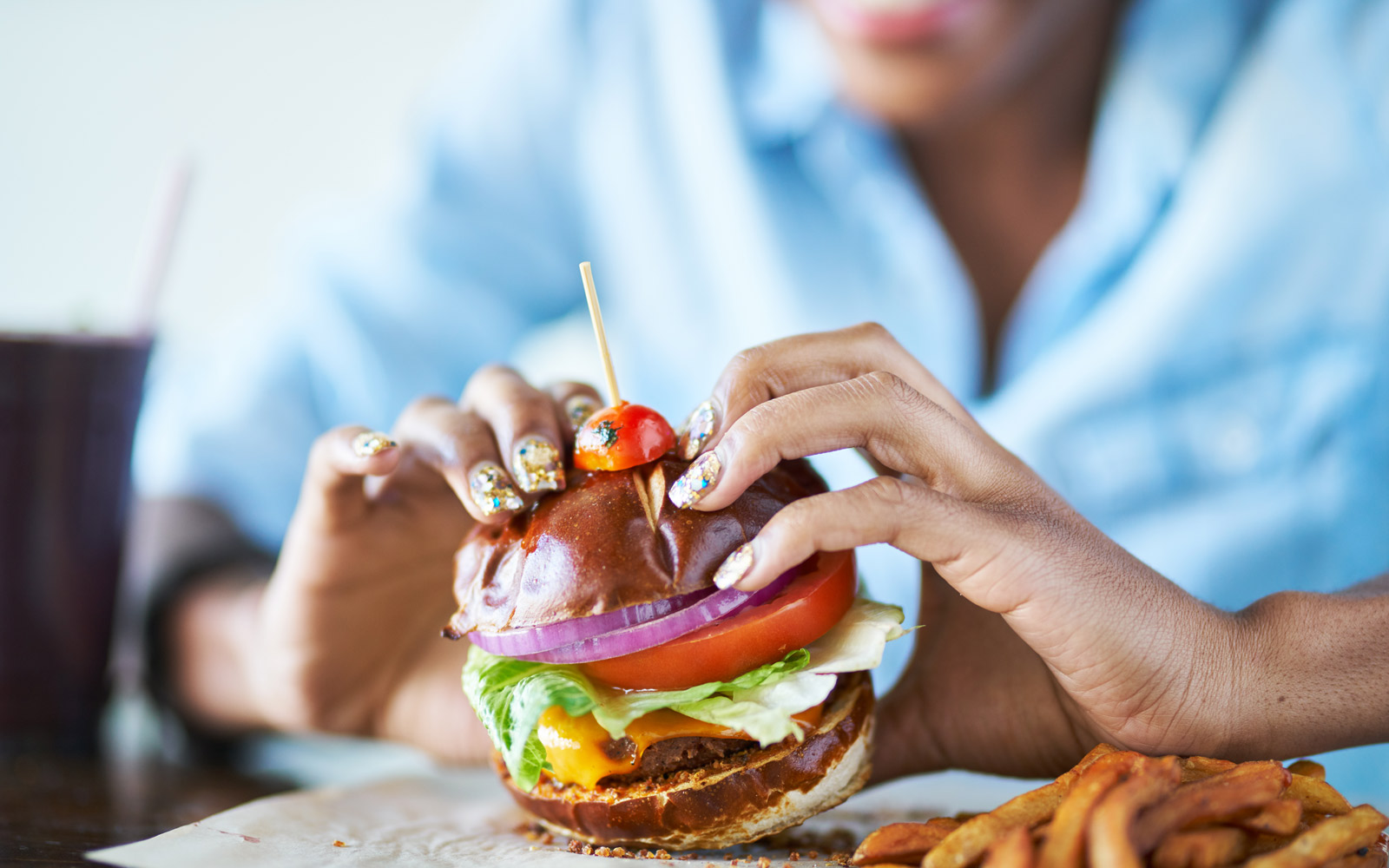 african american woman about to eat vegan meatless cheese burger at restaurant