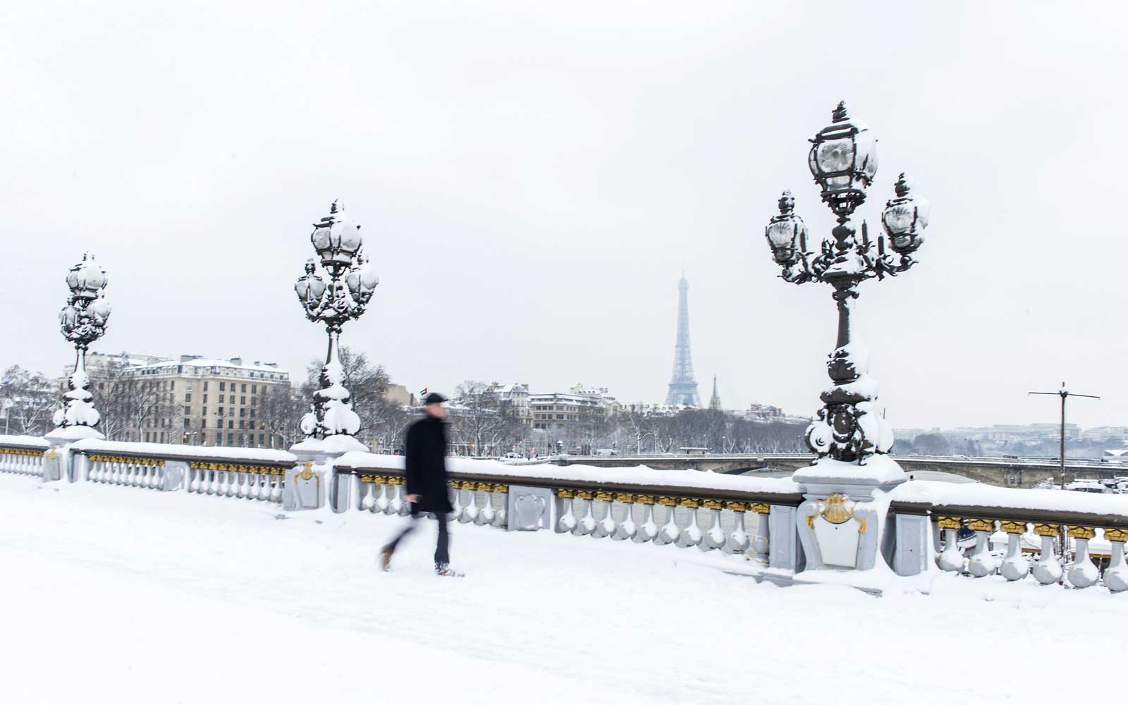 A man walks along a snow-covered bridge in Paris, France