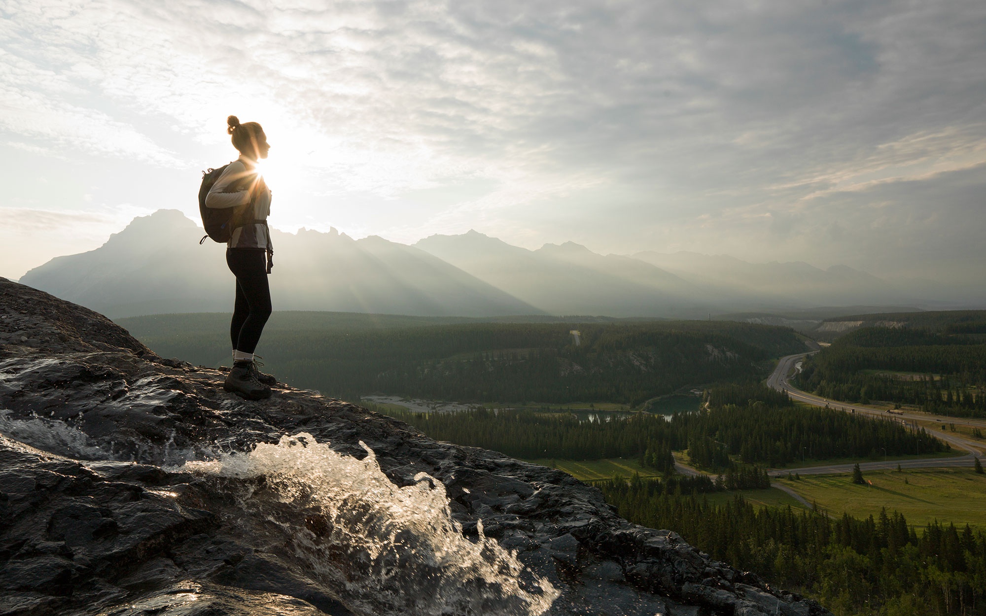 Young woman looks across mtns and valley, sunrise