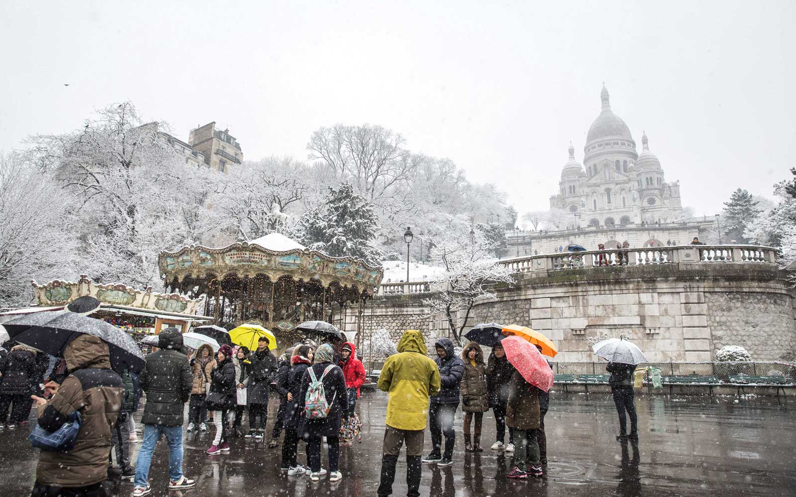 Tourists under the snow at the basilica of the Sacre Coeur on February 6, 2018 in Paris, France.