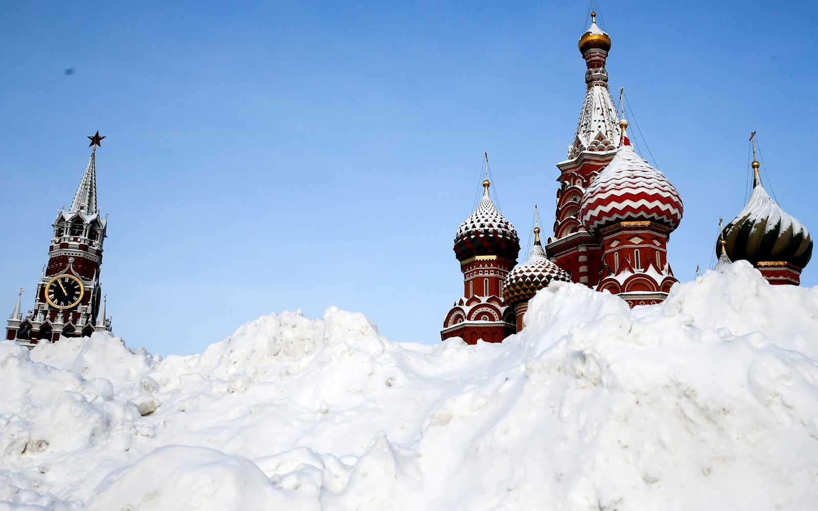 The snow hills are seen on the Vasilyevsky Spusk as Saint Basil's Cathedral and Spasskaya Tower are seen in the background following four days of snowfall in Moscow, Russia on February 06, 2018.