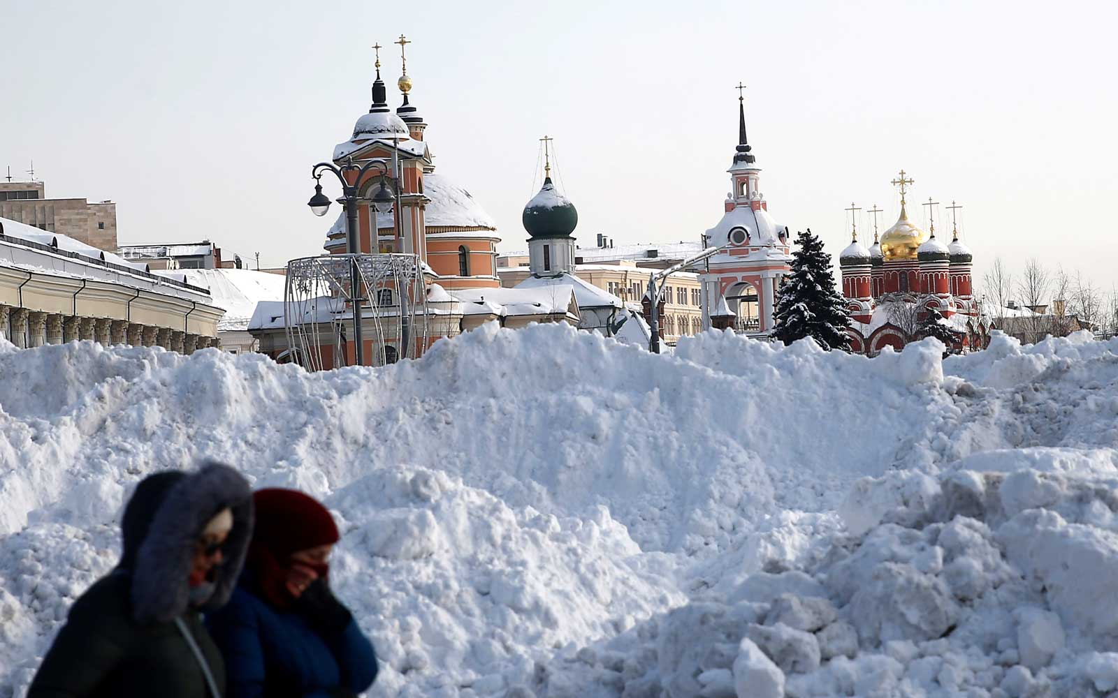 Two women walk at the Vasilyevsky Spusk as snow hills  are seen in the background following four days of snowfall in Moscow, Russia on February 06, 2018.