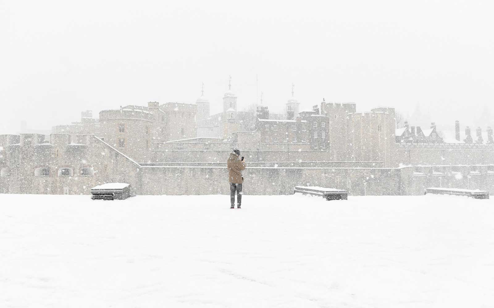 A man photographs the Tower of London in snowy conditions