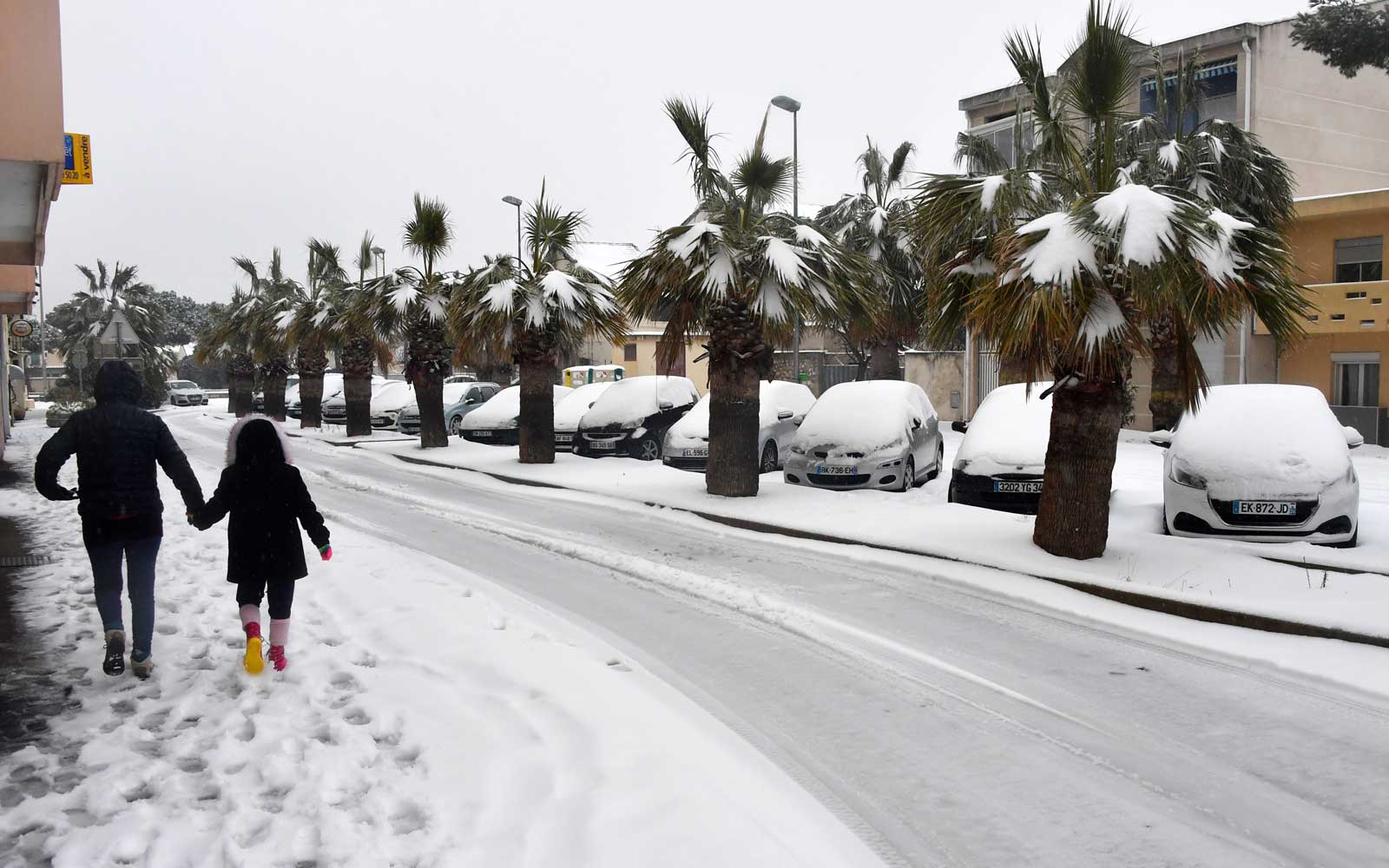 A woman walks with a child down a snow-covered road in Palavas-les-Flots, in the south of France, on February 28, 2018.