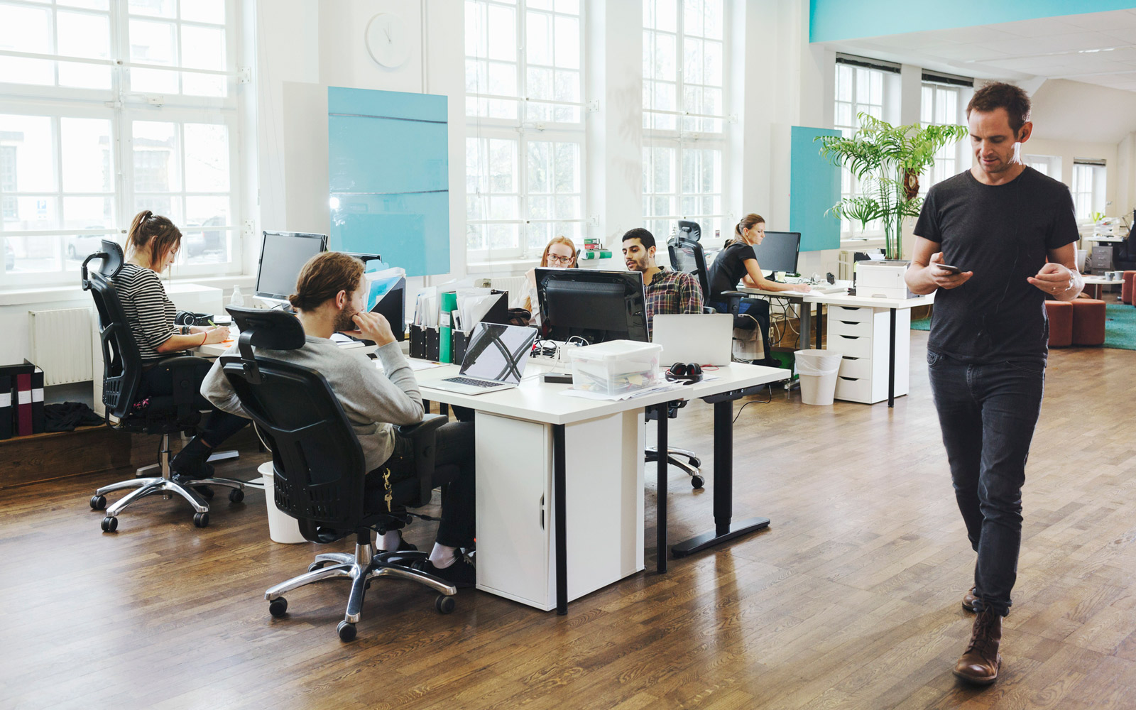 Businessman walking by colleagues working at desk in creative office