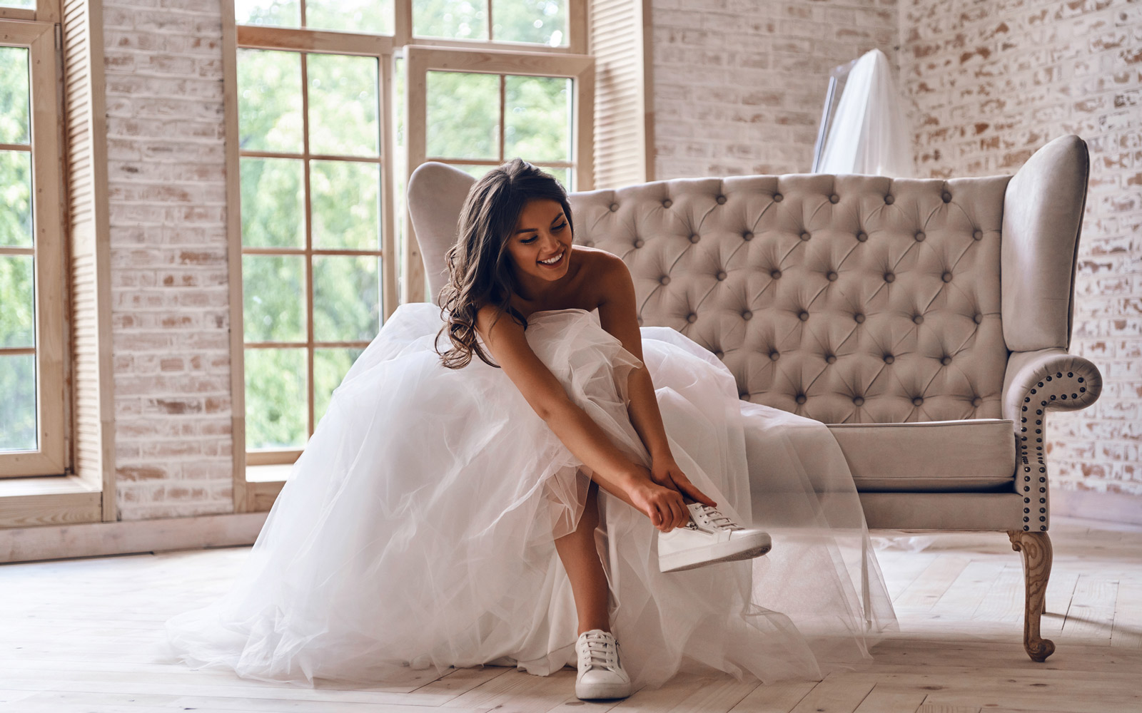 Attractive young woman in wedding dress putting on sports shoes and smiling while sitting on the sofa