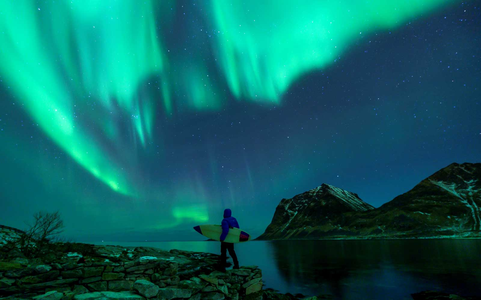 A surfer looks at Northern Lights on March 9, 2018 in Utakleiv, northern Norway, Lofoten islands, within the Arctic Circle.