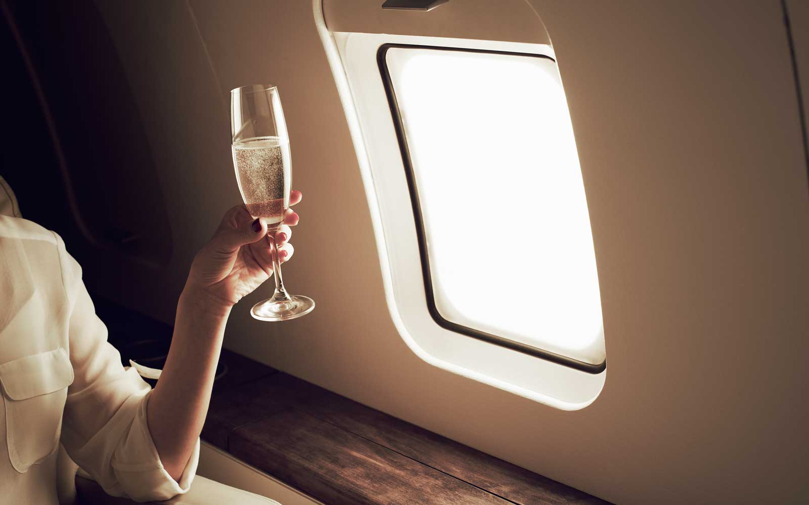 Woman holiding champagne on an airplane