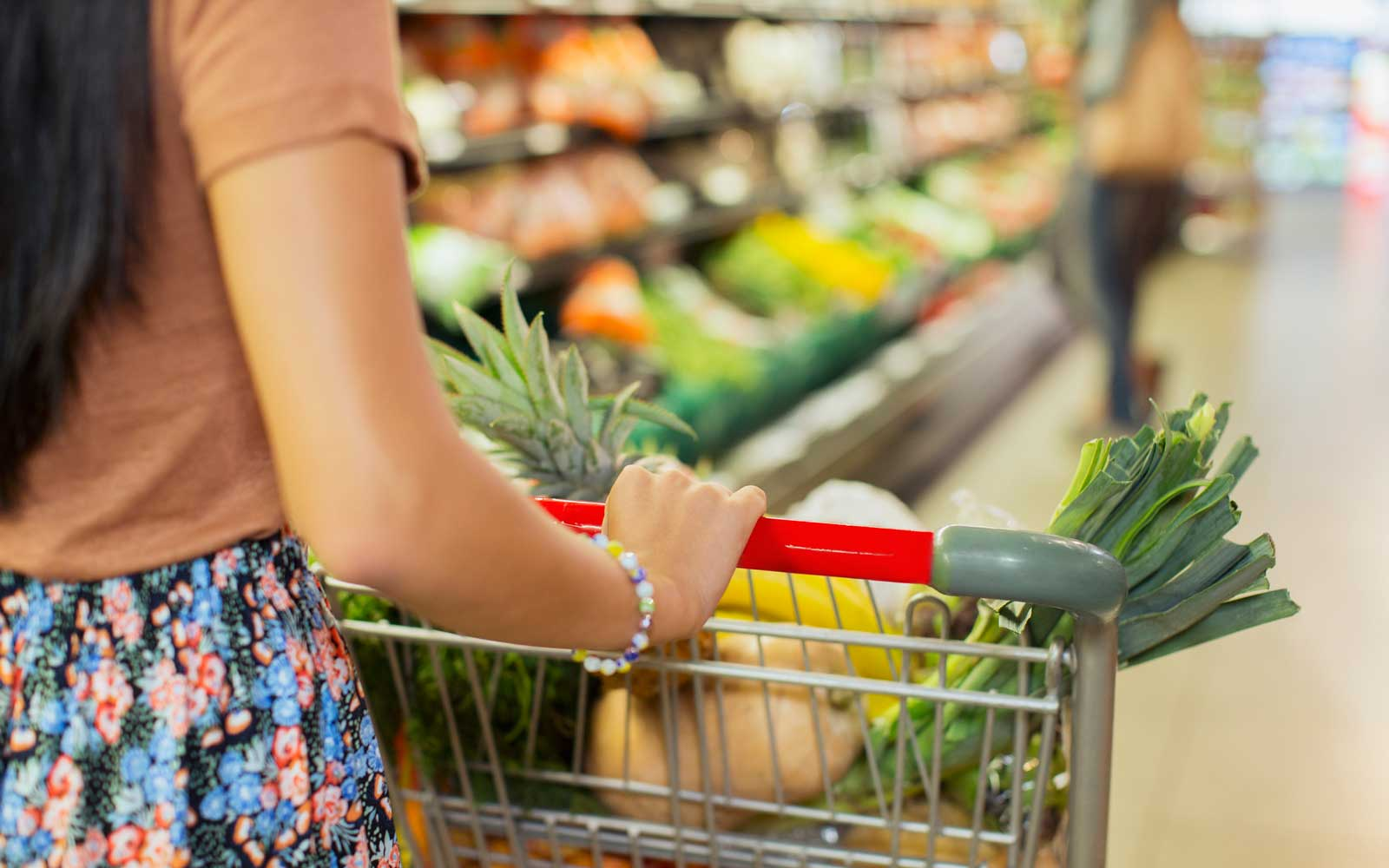 Close up of woman pushing full shopping cart in grocery store