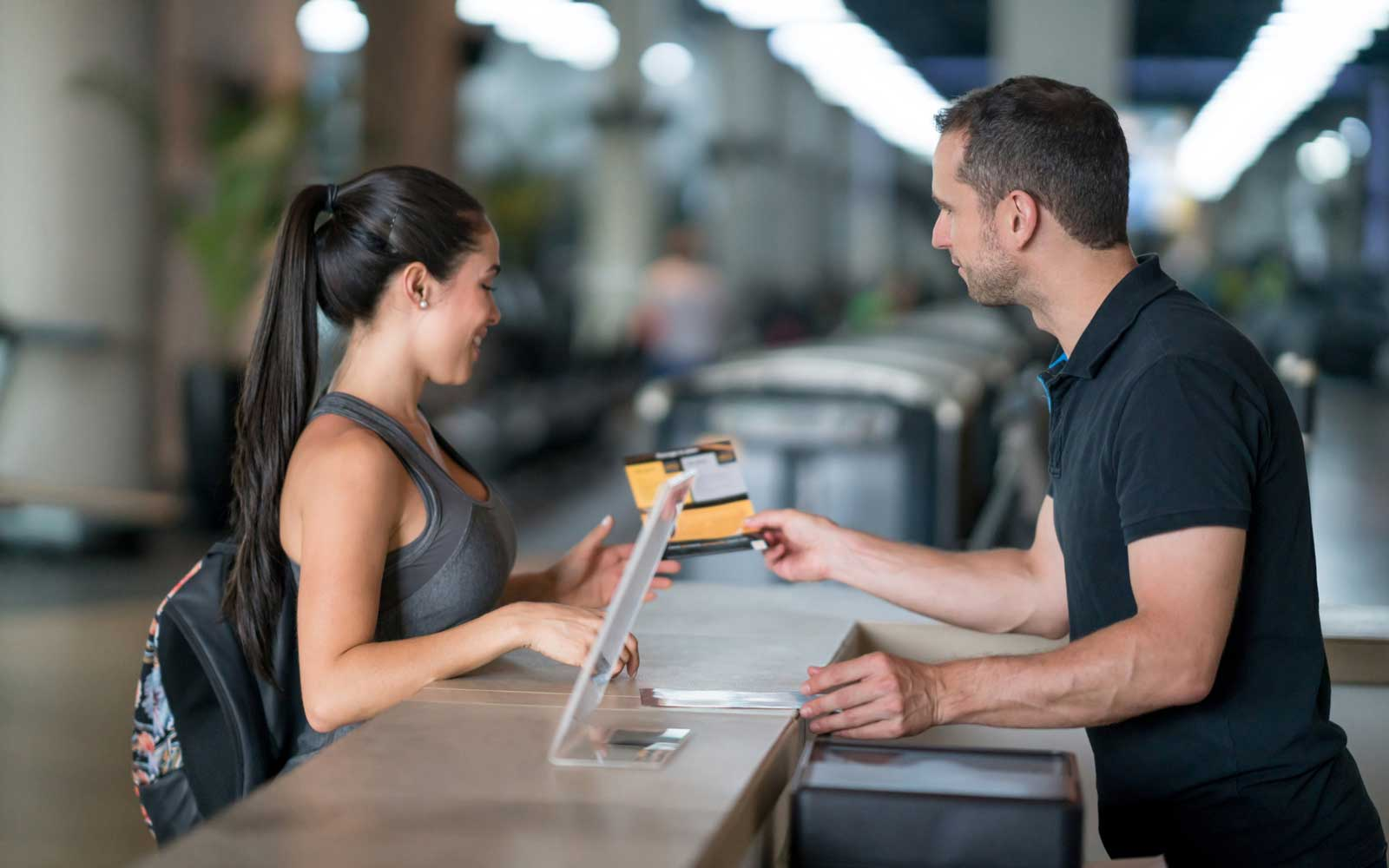 Woman at the gym talking to receptionist about membership plans