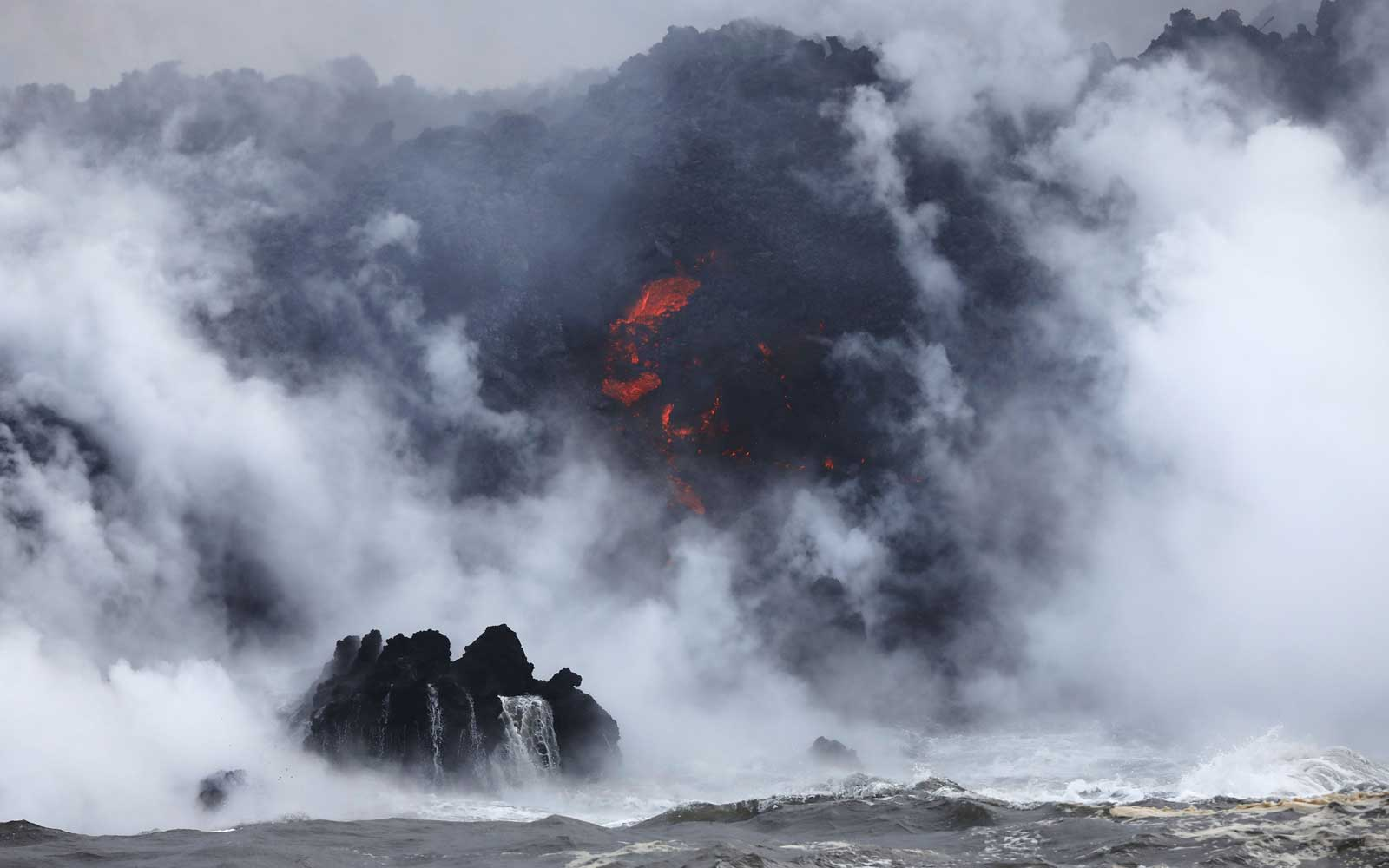 A steam plume rises as lava (C) enters the Pacific Ocean, after flowing to the water from a Kilauea volcano fissure, on Hawaii's Big Island