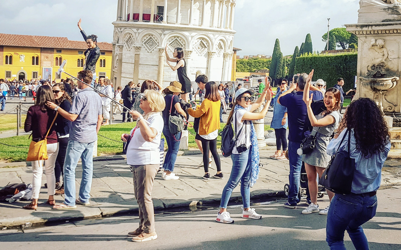 Tourists having fun as they pose for, and take photos of the Leaning Tower, with many people putting their hands out as if supporting the weight of the tower.