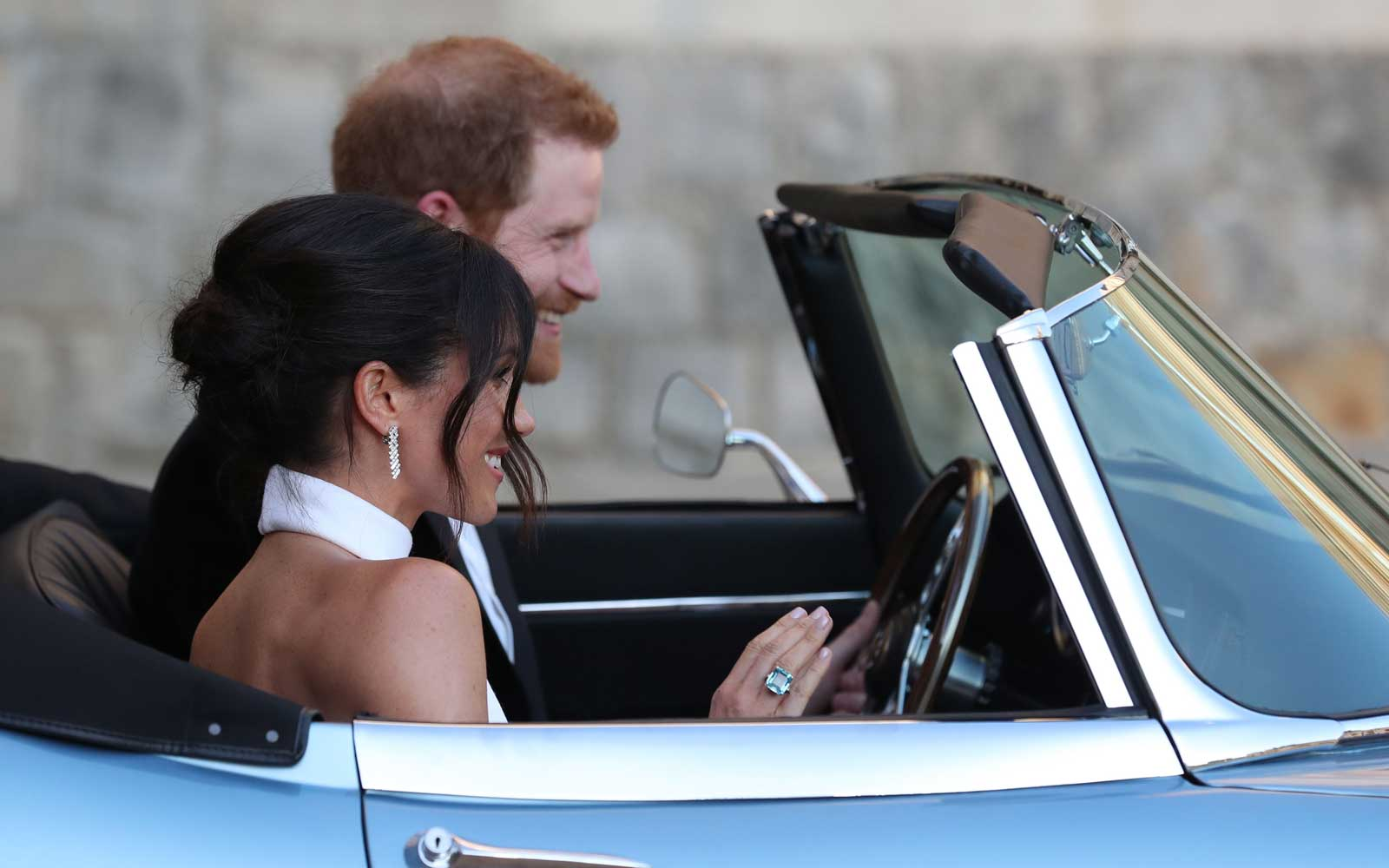 Britain's Prince Harry, Duke of Sussex and Meghan Markle, Duchess of Sussex leave Windsor Castle in Windsor on May 19, 2018 in an E-Type Jaguar after their wedding