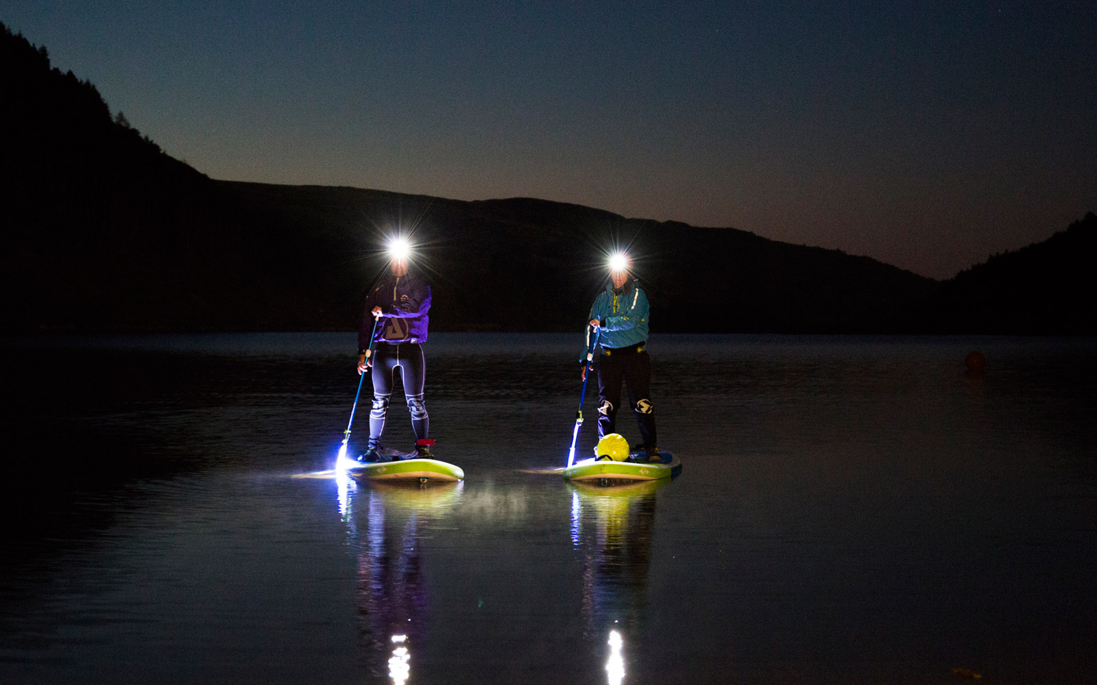 Stand-up paddleboard in the moonlight, in Wales, U.K.