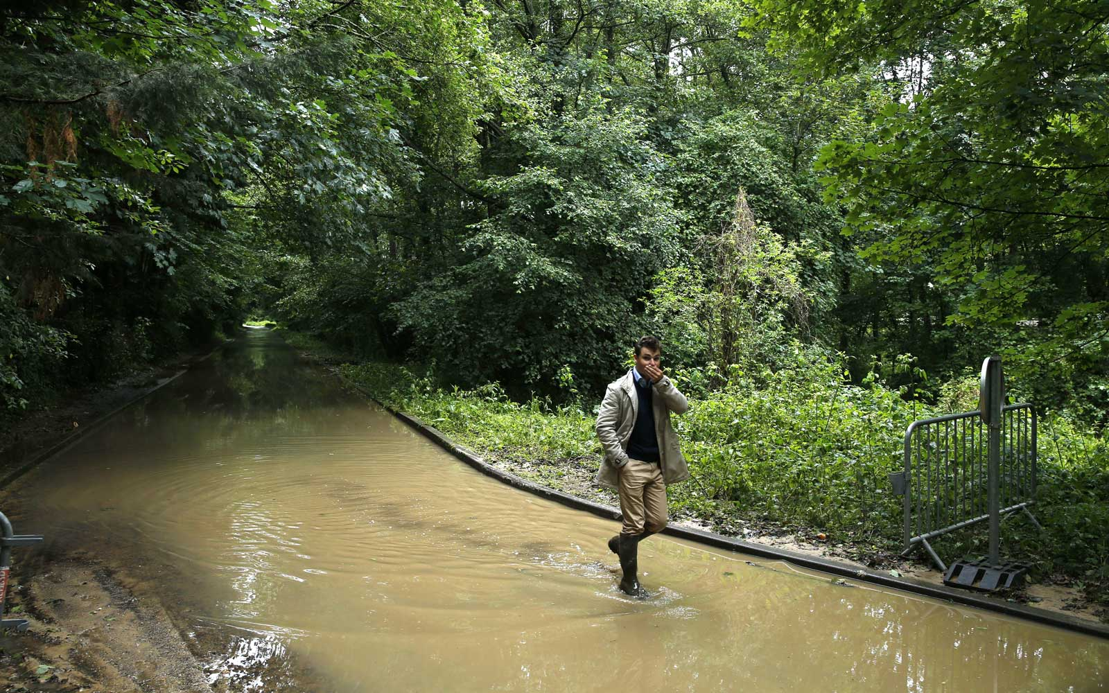 A man walks in a flooded road in Saint-Remy-les-Chevreuse on June 12, 2018 following heavy rains.