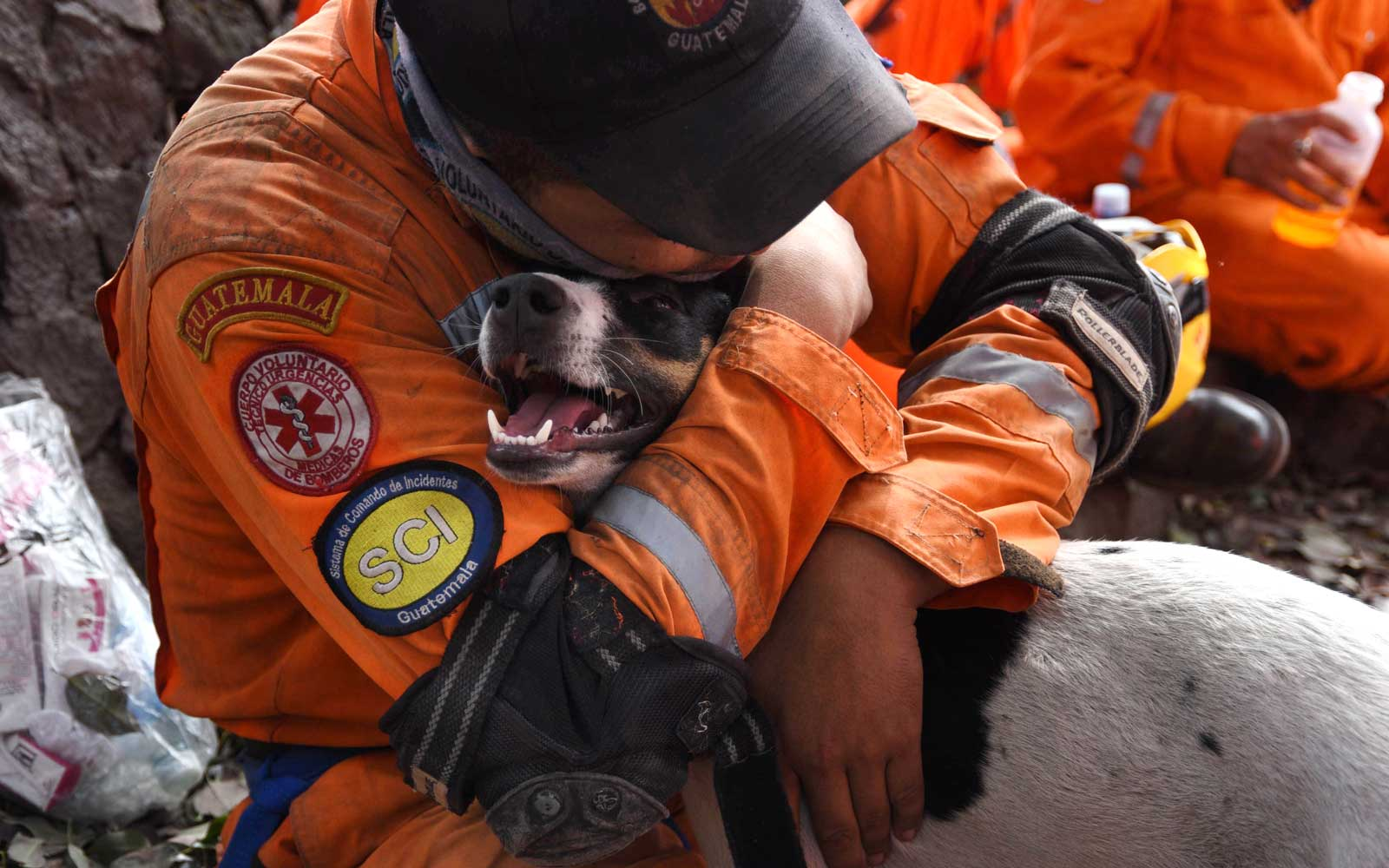 A volunteer firefighter hugs a dog during the search for victims of Sunday's Fuego Volcano eruption in Alotenango, a municipality in Sacatepequez Department, southwest of Guatemala City on June 6, 2018.