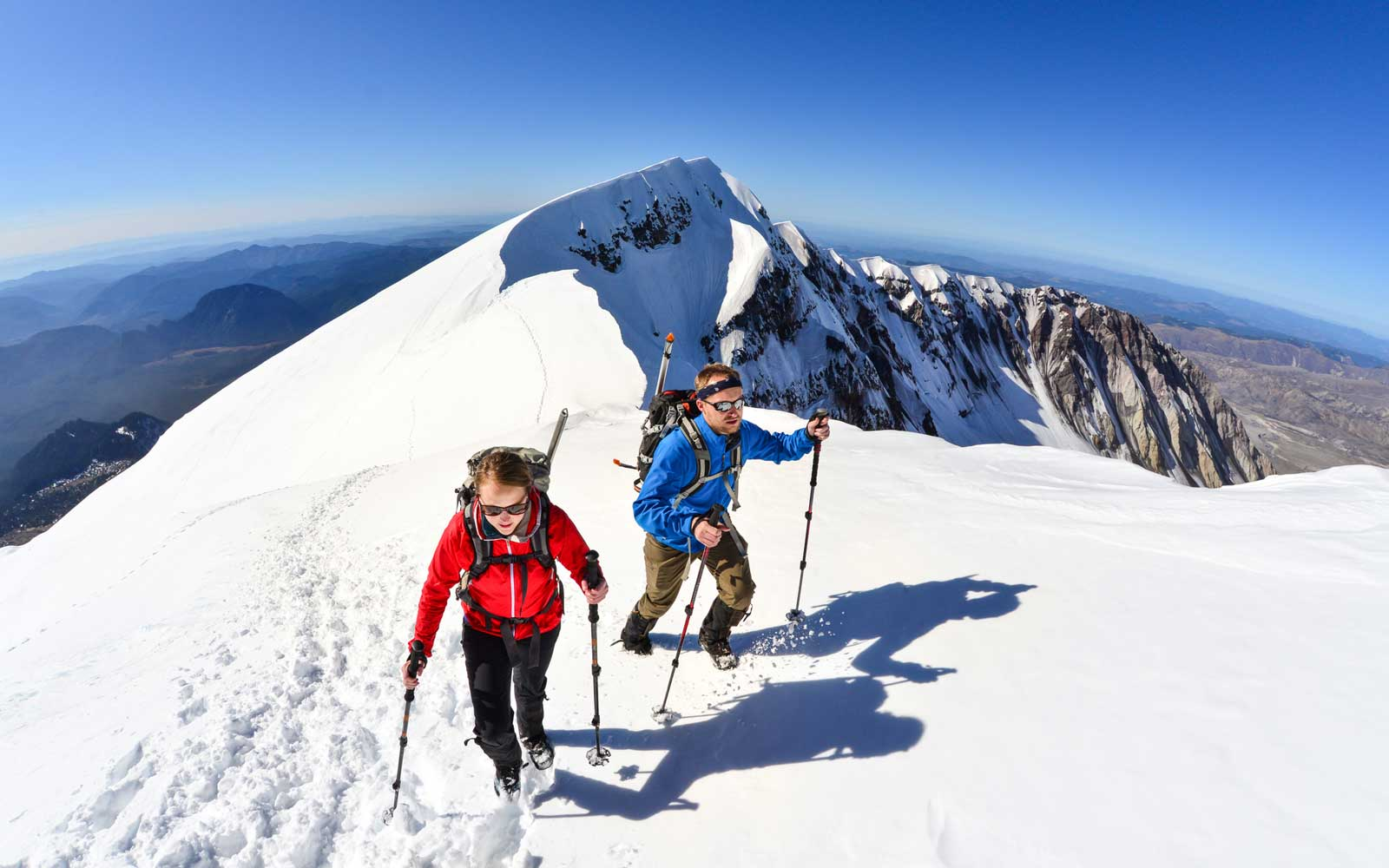 A woman and man traverse the summit ridge of Mt. St. Helens, Washington State.