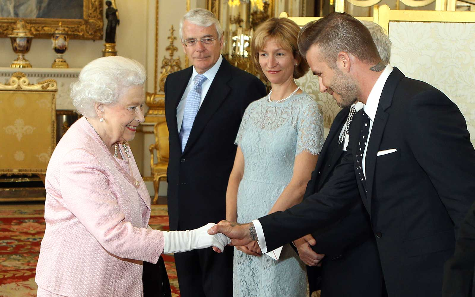 Britain's Queen Elizabeth II shakes hands with former England footballer David Beckham as in London on June 22, 2015