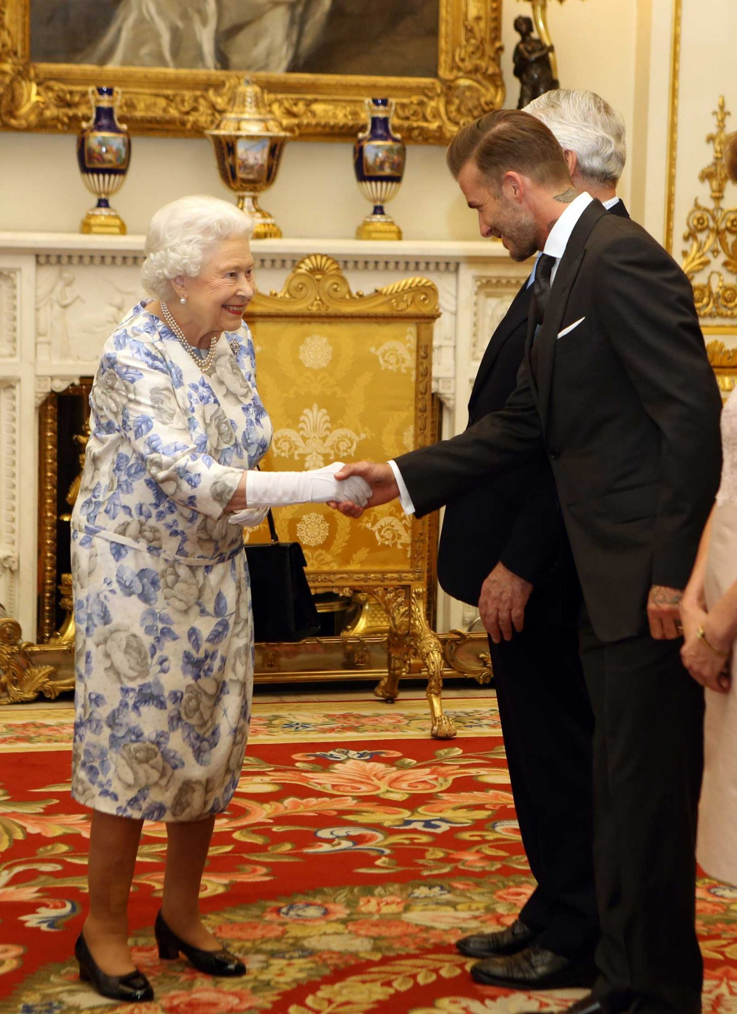 Britain's Queen Elizabeth II greets England's former football player David Beckham (R) as he attends the Queen's Young Leaders Awards at Buckingham Palace in London on June 23, 2016.