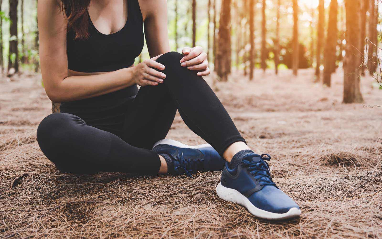 Girl has sport accident injury in forest at outdoors. Healthy and Medicine concept. Adventure and Travel concept. Pine woods theme.