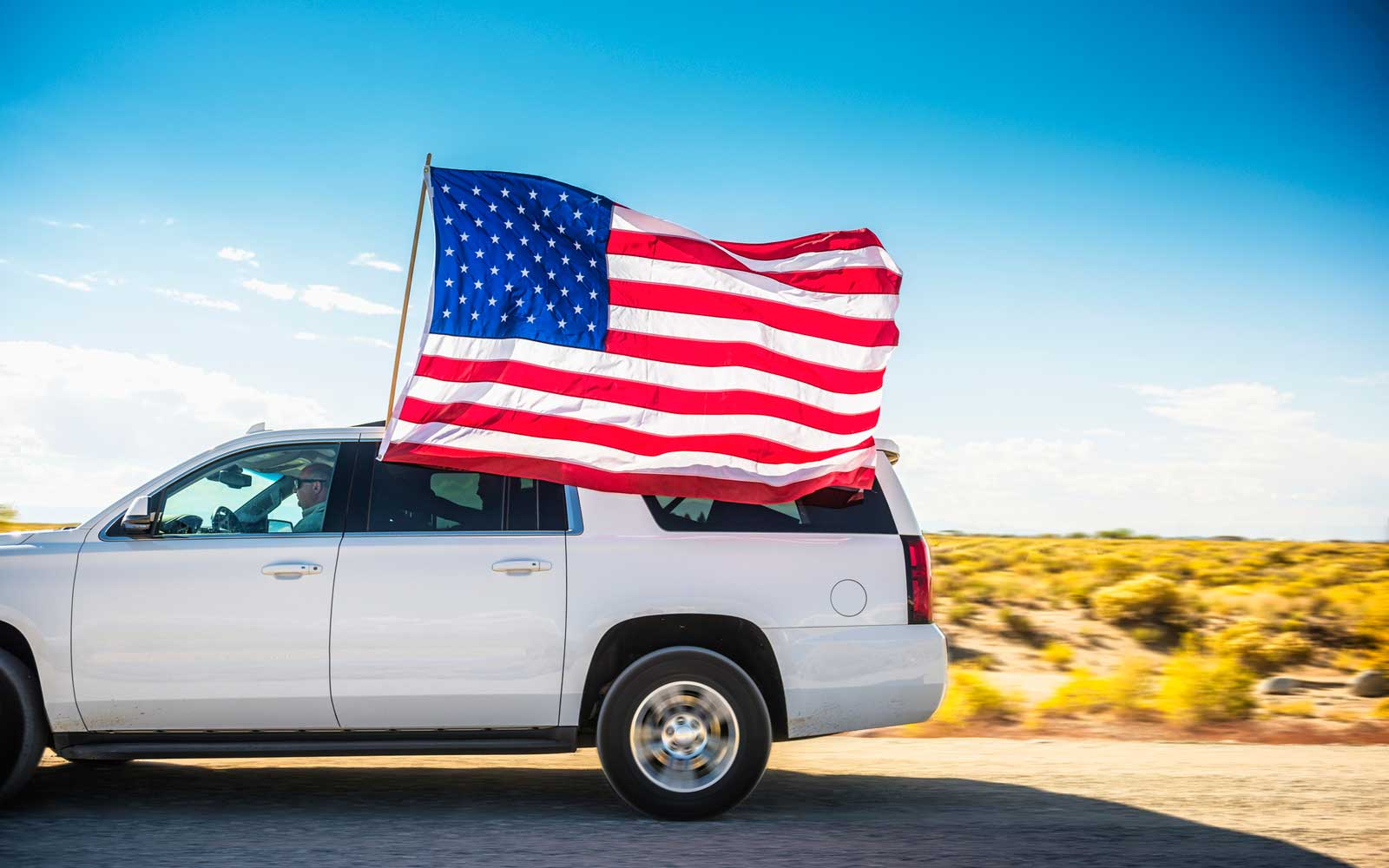 White SUV driving with passenger holding American flag