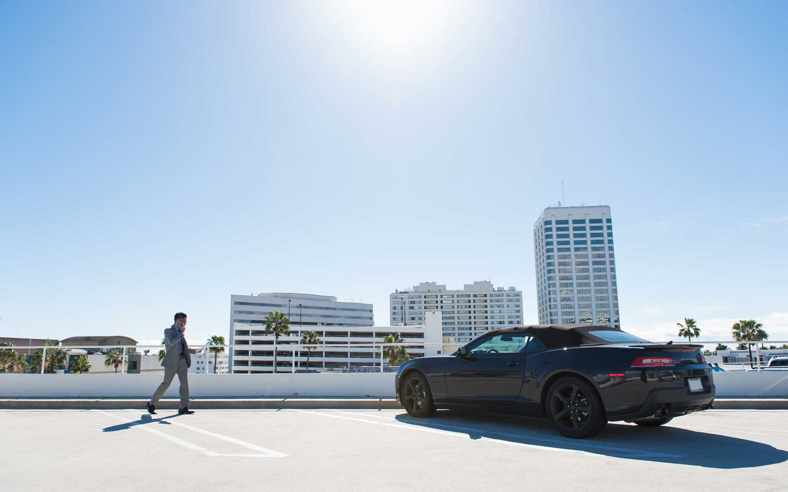Young businessman on city rooftop car park walking and talking on smartphone
