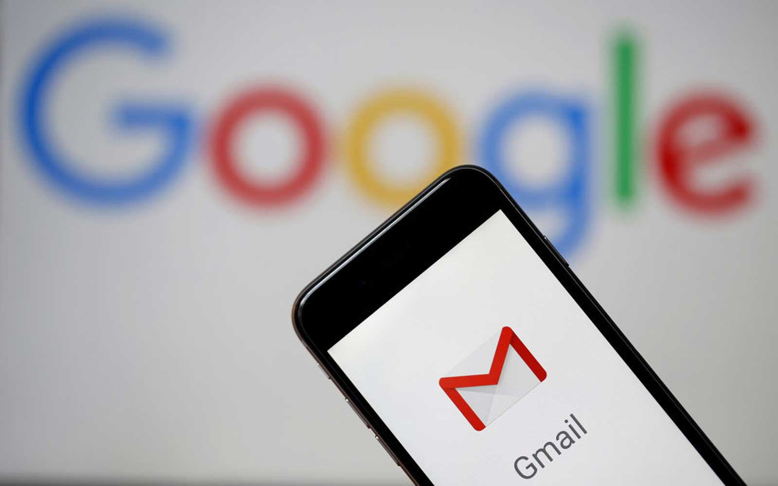 In this photo illustration, the logo of the Gmail app homepage is seen on the screen of an iPhone in front of a computer screen showing a Google logo on July 04, 2018 in Paris, France.