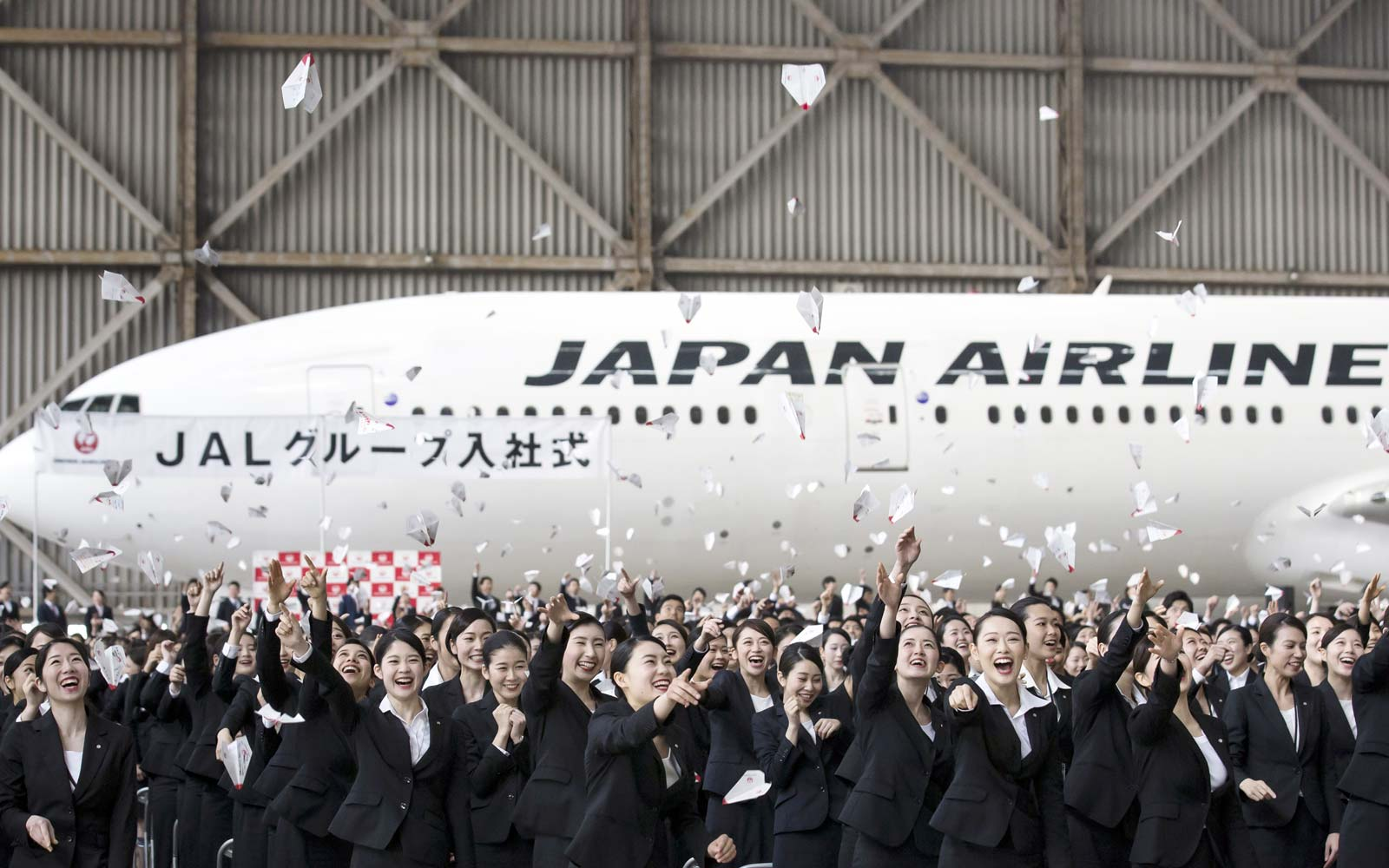 New Japan Airlines crew celebrate in front of a Boeing 777