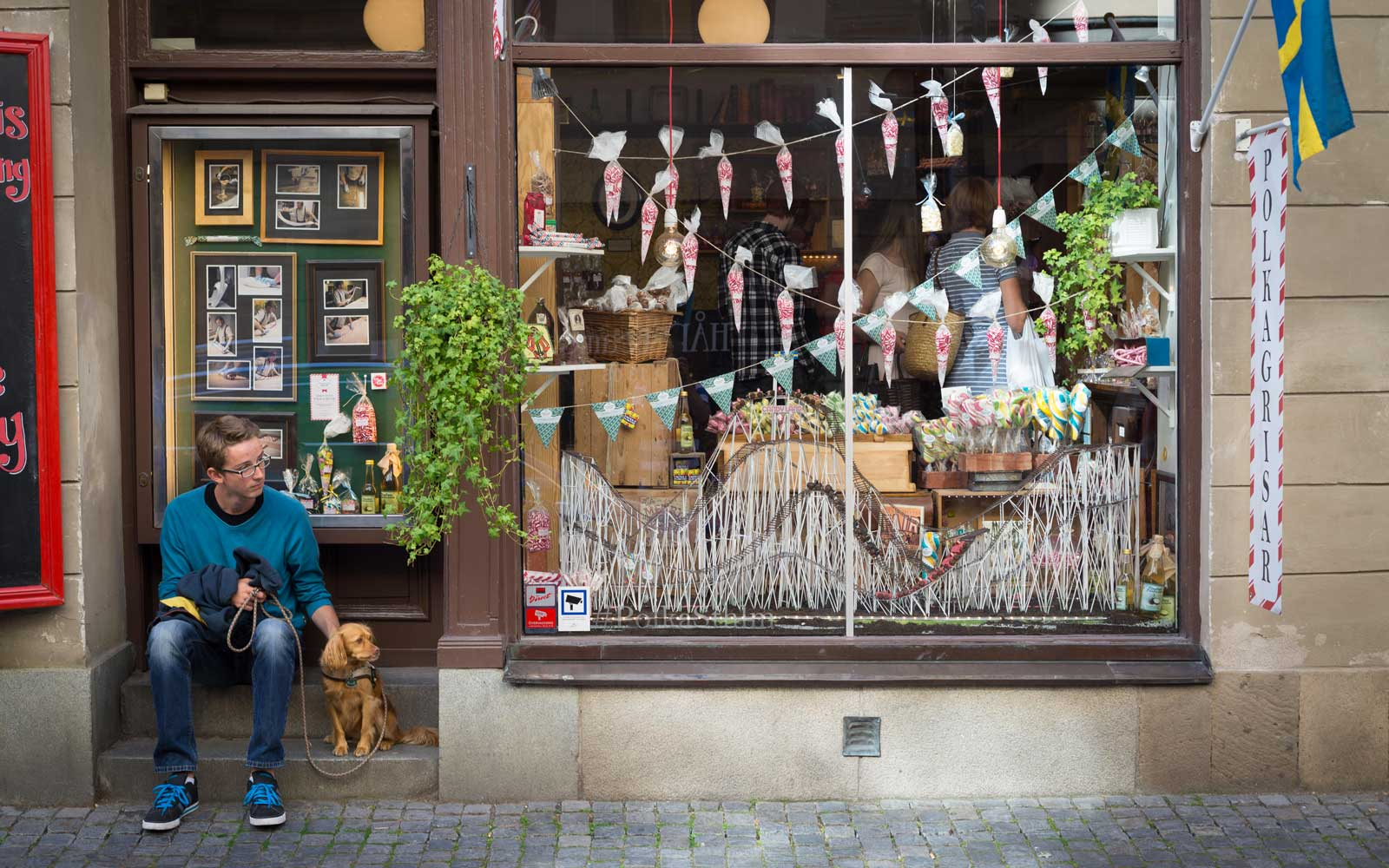 Young man sitting with dog waiting in a cobbled street in the old town at one of the oldest candy shops of Stockholm,Sweden