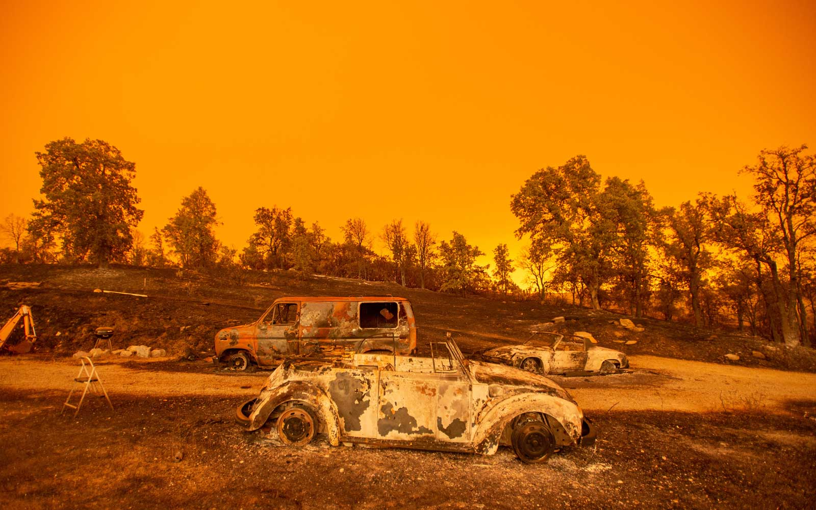 Burned down vehicles sit at a property under a deep orange sky during the Carr fire near Redding, California on July 27, 2018