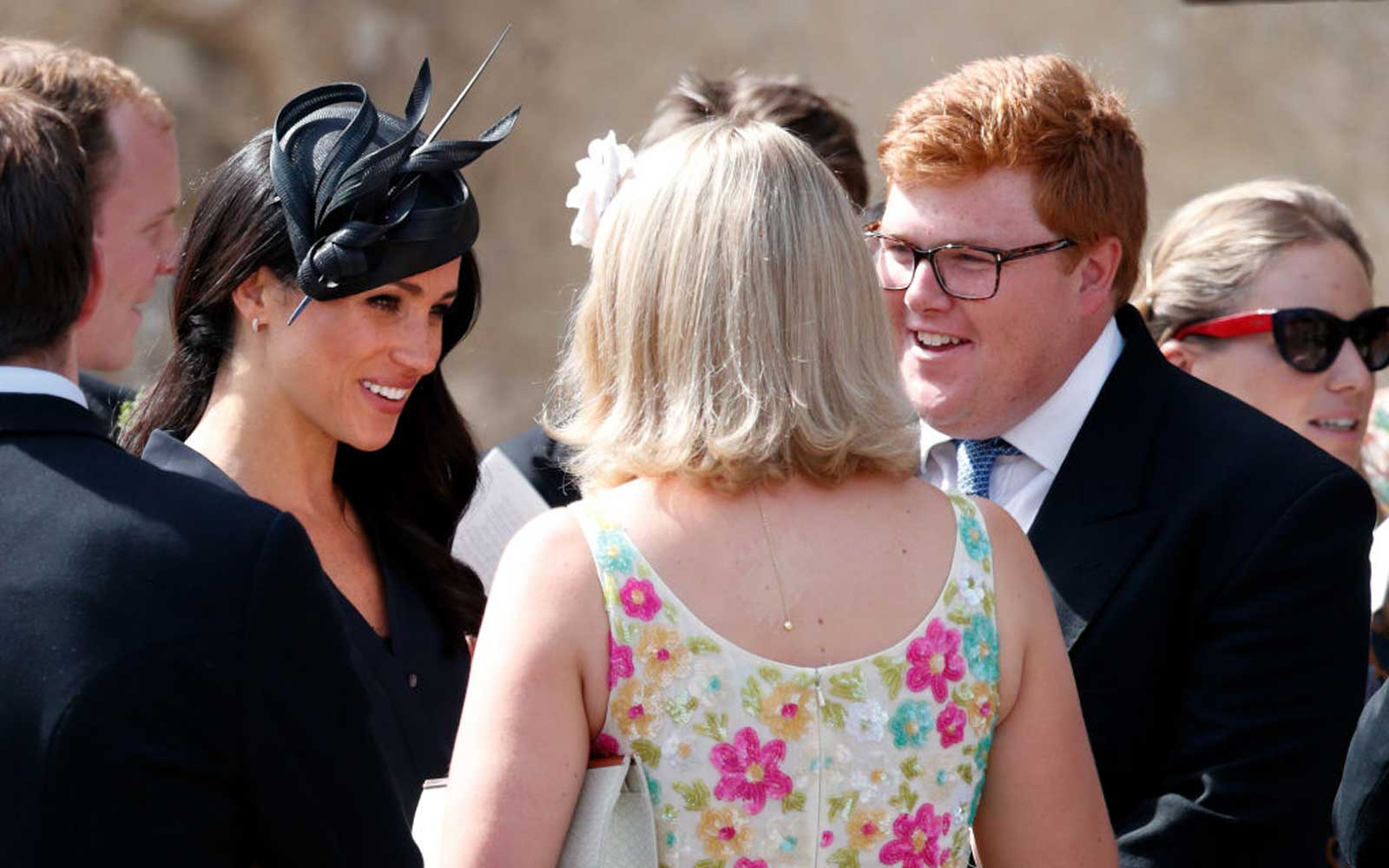Meghan, Duchess of Sussex talks with Celia McCorquodale and George Woodhouse as she attends the wedding of Charlie van Straubenzee and Daisy Jenks at the church of St Mary the Virgin