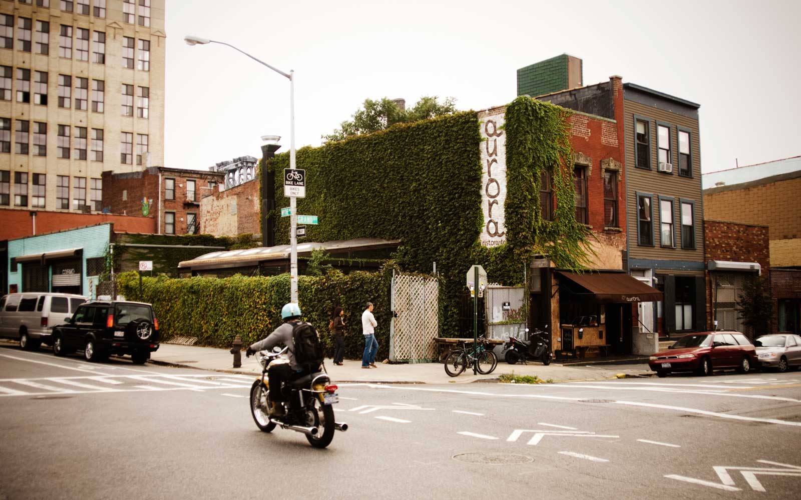 Man riding his motorcycle through an intersection in the streets of Williamsburg, Brooklyn, New York.