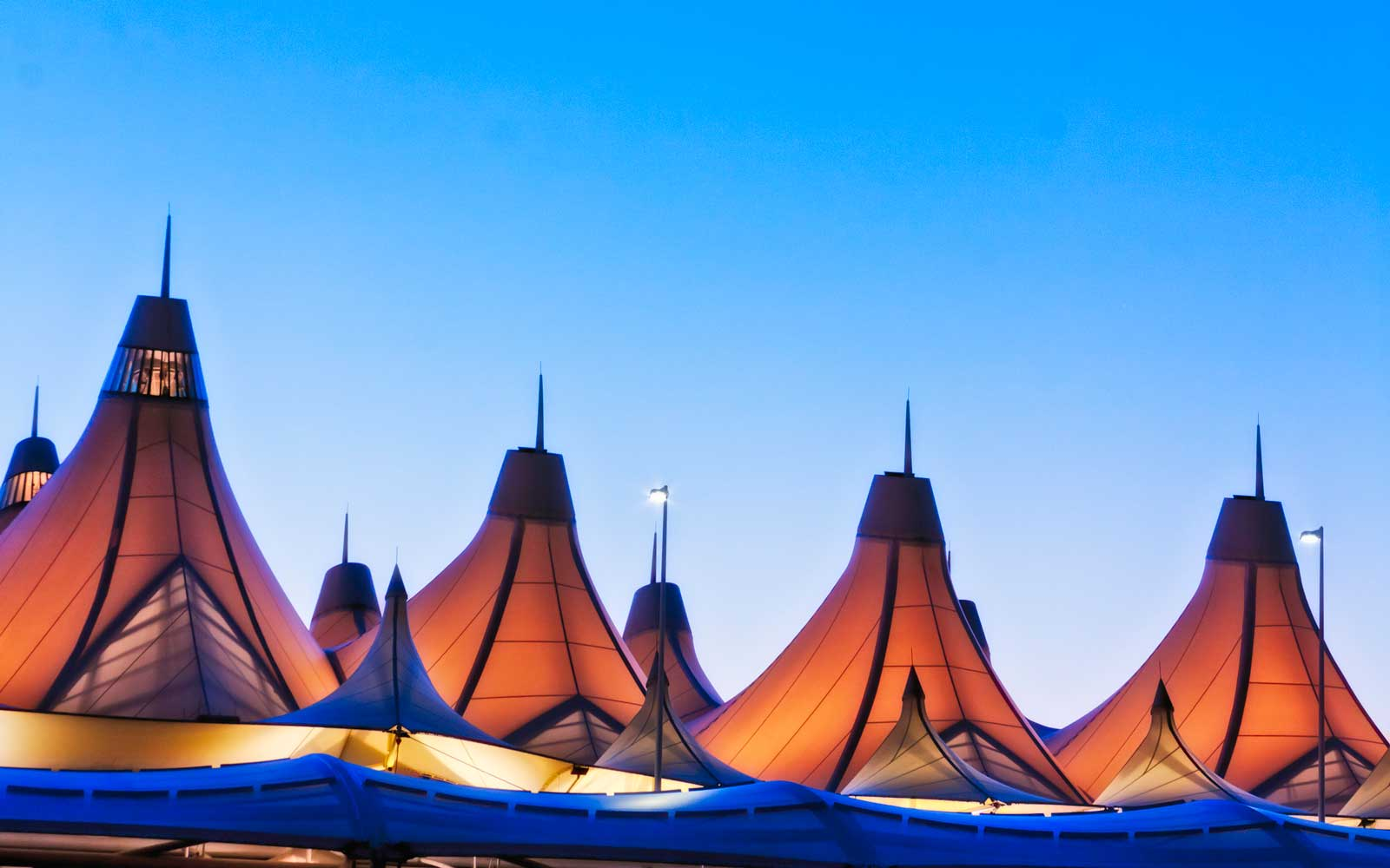 Denver International Airport lit during early morning blue hour