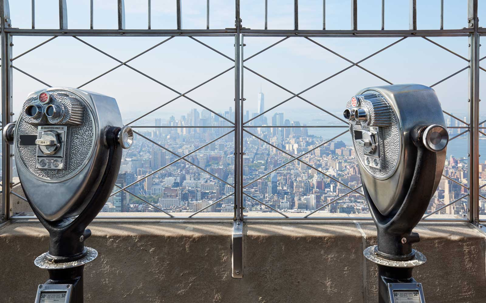 Empire State Building observation deck with two binoculars in a sunny day in New York