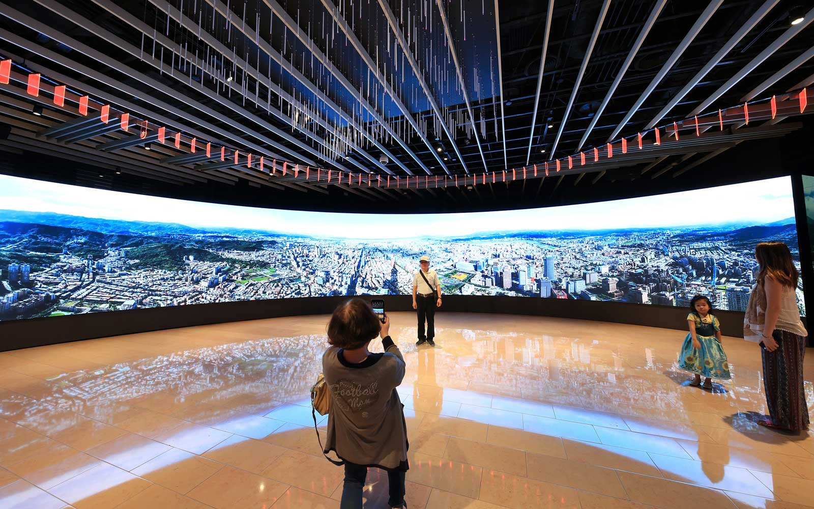 People enjoy taking pictures in front of the panorama tv screen inside of Taipei 101in Taiwan