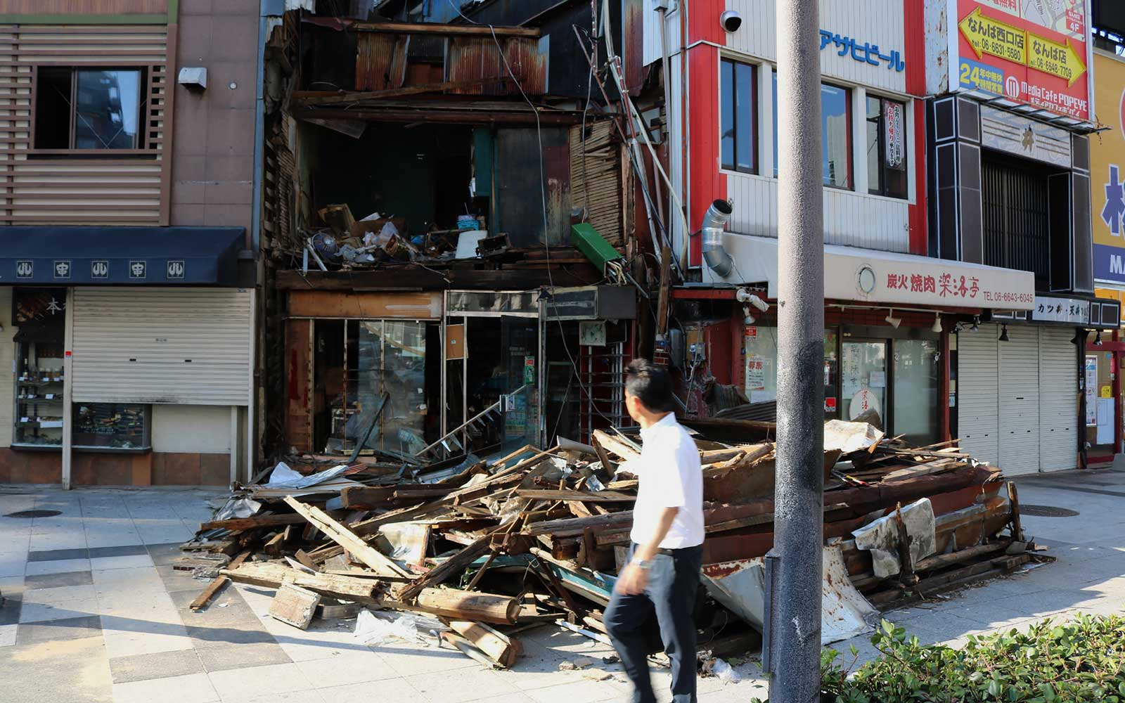 A man walks past a wooden house destroyed by strong winds from typhoon Jebi in Osaka on September 5, 2018.