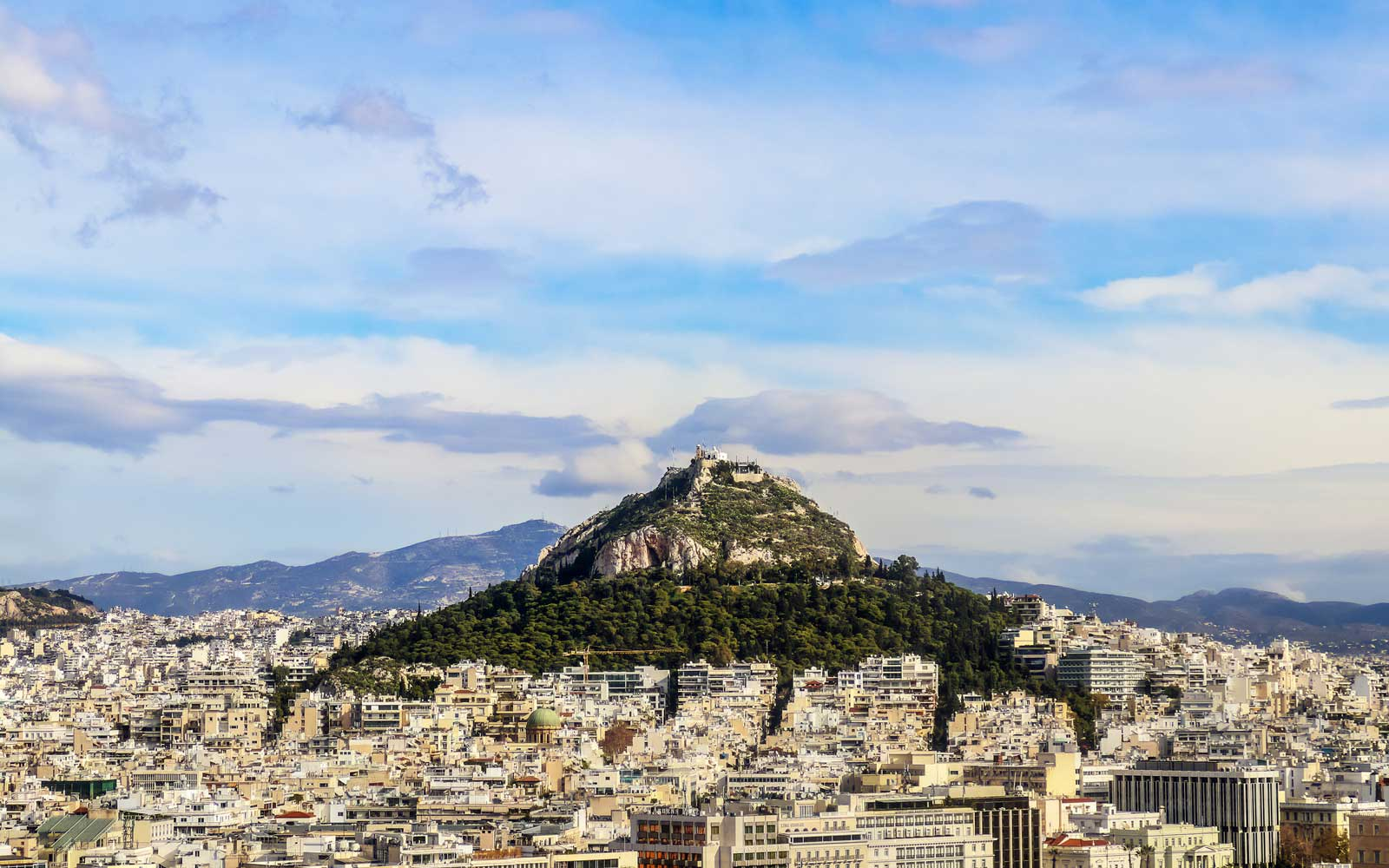 Looking over the rooftops to Lycabettus Hill - the highest spot in Athens Greece with church of St George and a resturant where tourists can enjoy the view