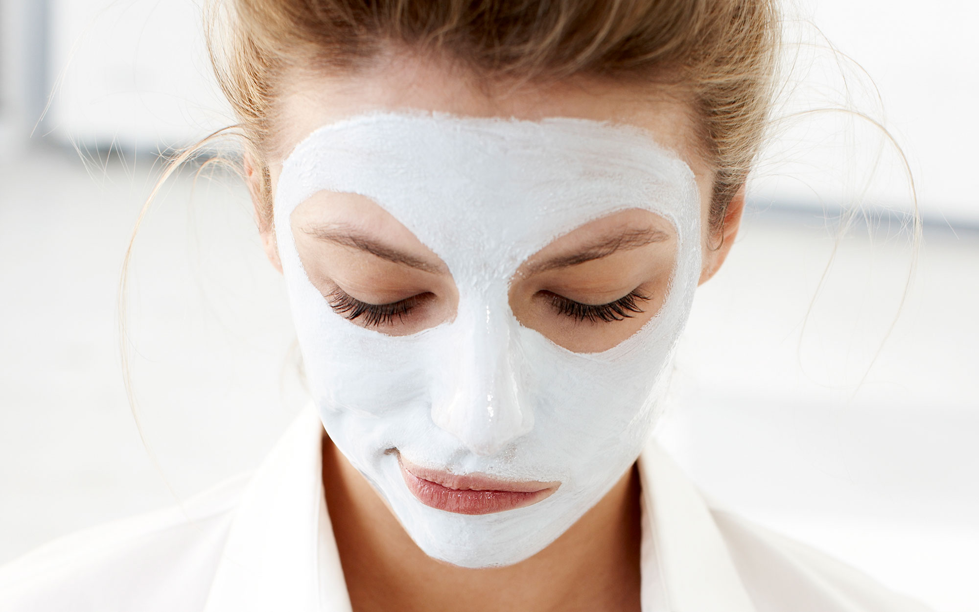 Woman with facial mask using cell phone