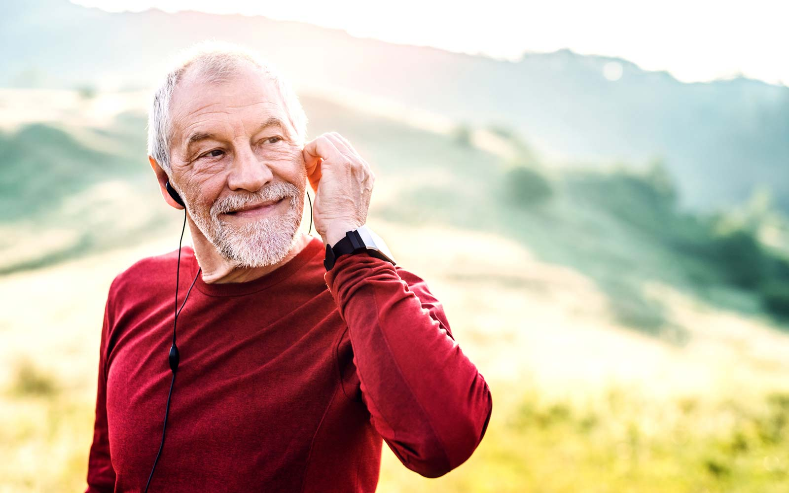 A portrait of an active senior man with earphones outdoors in nature in the foggy morning. Copy space.