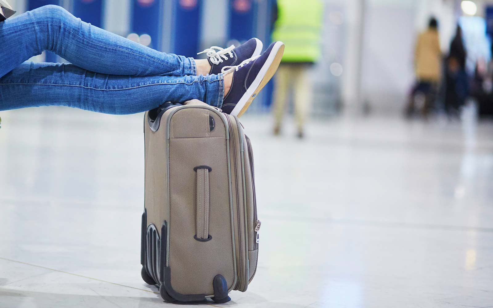 Closeup of woman feet on a suitcase in international airport