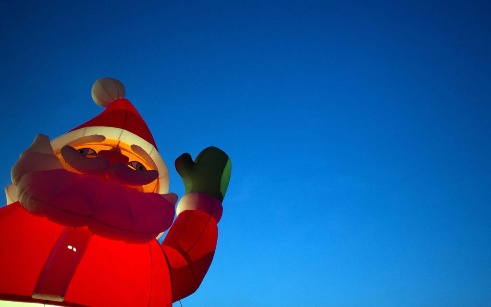 An inflatable Santa Claus glows at a Christmas tree stand