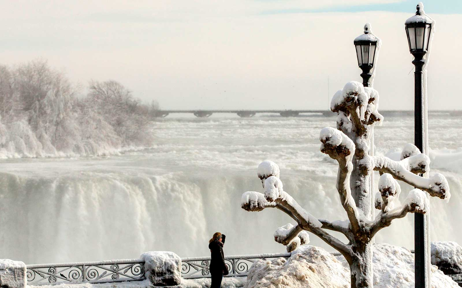 Tourists look out past the frozen railings at the Horseshoe Falls in Niagara Falls, Ontario on January 3, 2018.