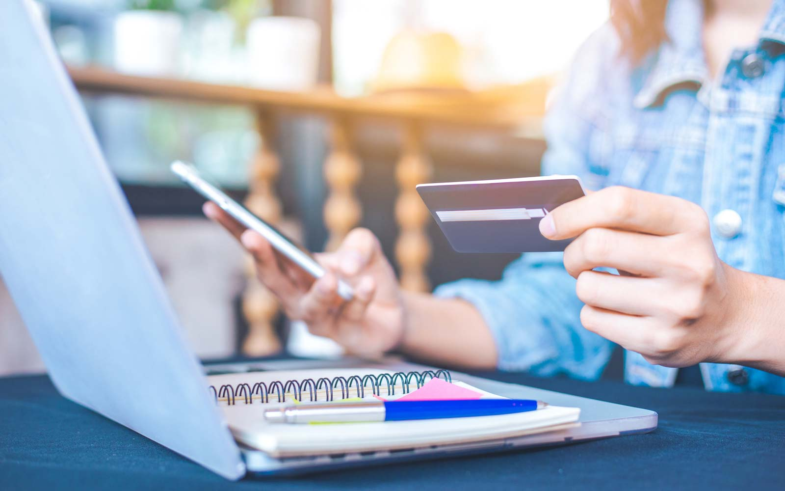 Women hold credit cards and use mobile phones to shopping online.