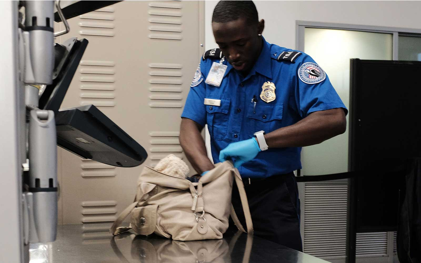 A Transportation Security Administration (TSA) worker screens passengers at LaGuardia Airport (LGA)