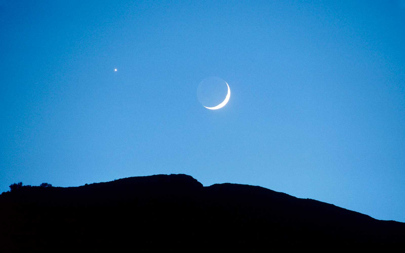 Drome, France - View of planet Venus and a crescent moon above a mountain at Joncheres in the Diois.
