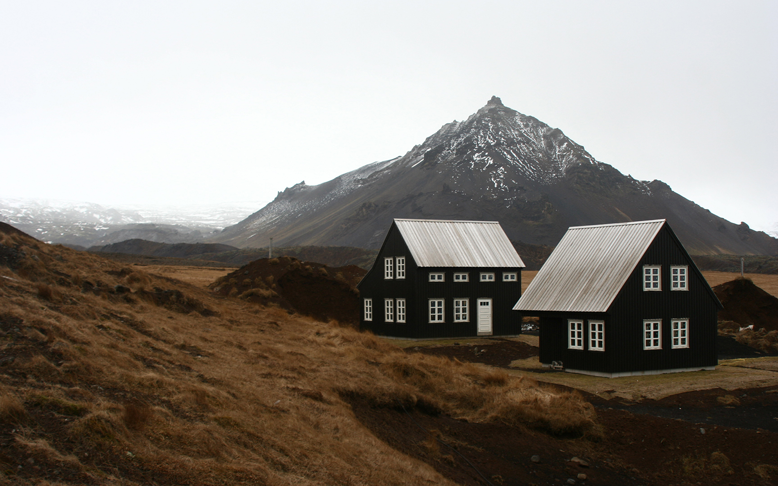 homes in the rugged landscape in Hellnar, Iceland