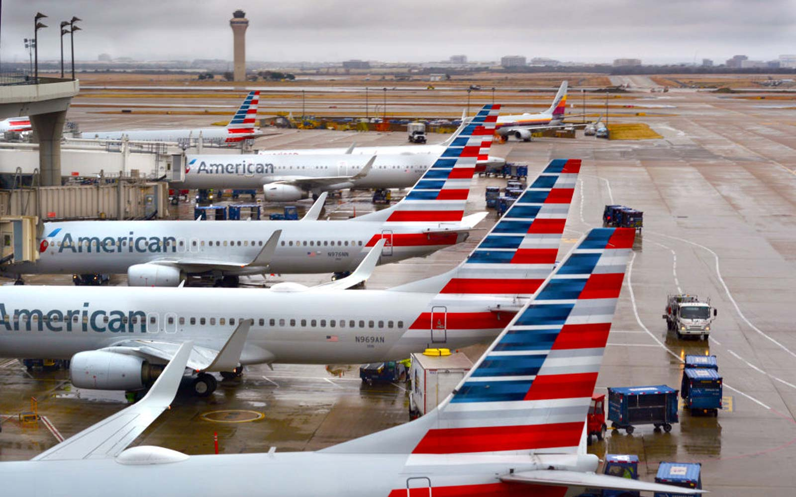 American Airlines passenger jets parked at their gates on a rainy morning at Dallas/Fort Worth International Airport